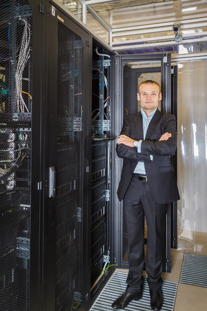 nas: IT Engineer in a suit stands next to the network equipment in the Data Center Stock Photo