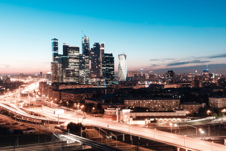 high-rise buildings and transport metropolis, traffic and blurry lights of cars on multi-lane highways and road junction at night in Moscow Stock Photo