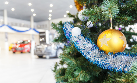 Colored Christmas balls on branch Christmas tree in showroom with new car in the background