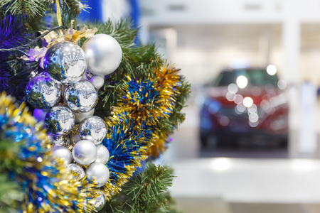 colored christmas balls on branch christmas tree in showroom with new car in the background stock