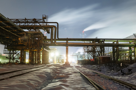 many pipes and smokestacks with industrial tower of metal on the chemical industry at night Stock Photo