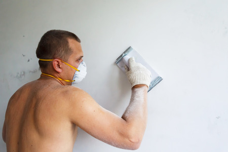 Plasterer at indoor renovation decoration with putty knife Stock Photo