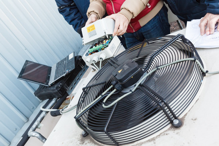 Cooling of industrial air conditioners, fans on the condenser. Engineer repairing a condenser fan control unit. Stock fotó