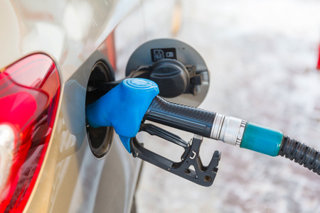 Gas pump nozzle in fuel tank of anew car, refuel Stock Photo