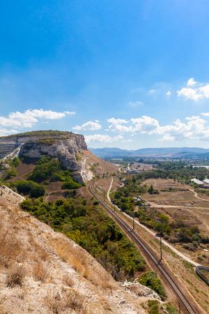 pit fall: Railway in mountainous landscape and Zagaytanskaya rock, Inkerman, Crimea, Russia