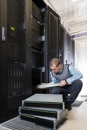 nas: IT Engineer installs JBOD to rack in datacenter