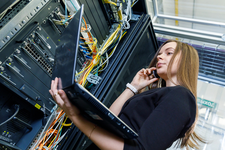 nas: Young woman engineer at the network equipment Stock Photo