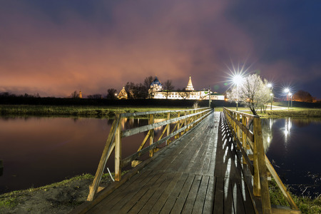 humildad: Suzdal, Russia. Nativity Cathedral, the bell tower and Archbishops chambers of Suzdal Kremlin at night in summer and wooden bridge Foto de archivo