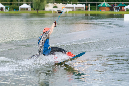 Beautiful young girl wakeboarding at lake Stock Photo