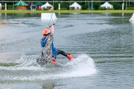 waterskiing: Beautiful young girl wakeboarding at lake Stock Photo