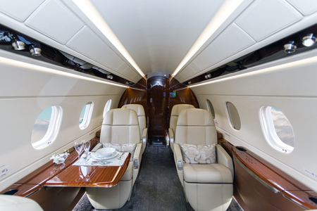Luxury interior in bright colors of genuine leather in the business jet, sky and clouds through the porthole Stock Photo