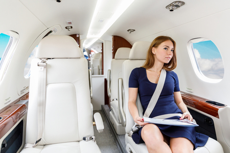 high tech: young beautiful woman in Luxury interior in bright colors of genuine leather in the business jet, sky and clouds through the porthole