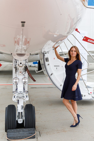 high tech: young beautiful woman stands next to the ladder and chassis the business jet