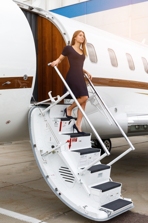 high tech: young beautiful woman going down the ladder from the business jet