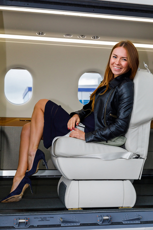 high tech: young beautiful woman in Luxury interior in bright colors of genuine leather in the business jet Stock Photo