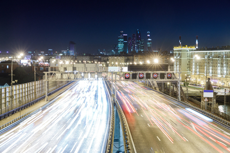 bandwidth: View of transport metropolis, traffic and blurry lights of cars on multi-lane highways and road junction at night in Moscow
