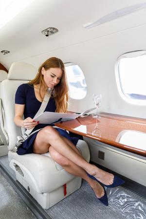 jonge mooie vrouw in luxe interieur in felle kleuren van echt leer in de zakenjet, lucht en wolken door de patrijspoort