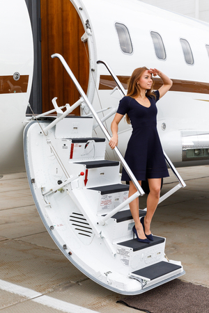 young beautiful woman going down the ladder from the business jet