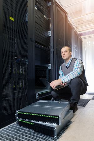 IT Engineer rack mount many hard disks drive in enclosure in the storage system in the data center and looks at the documentation on the laptop.