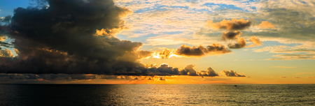 Dramatic sky during a hurricane and sunset over the ocean.