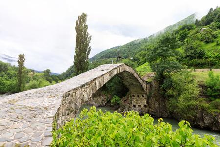 The stone arched bridge over the mountain river in Georgia. Stock Photo