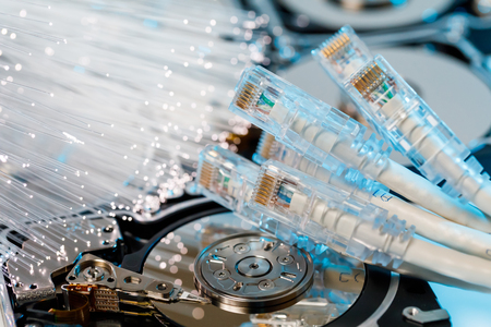 Server hard disks, illuminated optical fiber with blurred lights and closeup of RJ45 UTP LAN on the background of optical fibers with blurred lights
