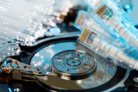 Server hard disks, illuminated optical fiber with blurred lights and closeup of RJ45 UTP LAN on the background of optical fibers with blurred lights