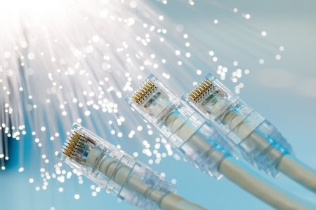 Closeup of RJ45 UTP LAN on the background of optical fibers with blurred lights.