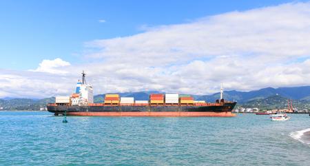 Een kleine container in de haven van Batumi op een achtergrond van bergen. Stockfoto
