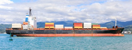 A small container in the port of Batumi on a background of mountains.
