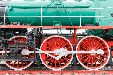 red wheel and detail of mechanism a vintage russian steam train locomotive. Stock Photo