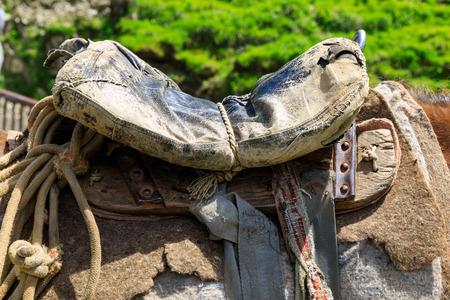 Threadbare old saddle on a shepherds horse, handmade saddle of a peasant shepherd.