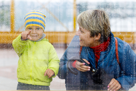 rainy weather and a little boy with his mother behind the glass, drops of rain on the window.