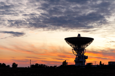 huge white radio telescope of a satellite dish against the sky during sunset.