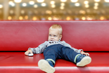 Child is lying on the couch in the shopping center or mall. Little boy tired during shopping with parents. Archivio Fotografico