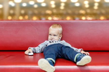 Kind liegt auf der Couch im Einkaufszentrum oder Einkaufszentrum. Kleiner Junge müde beim Einkaufen mit den Eltern.