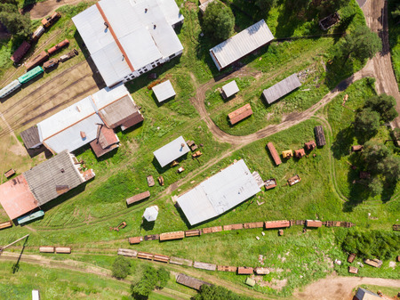abandoned railway station of narrow gauge railway, Branches of the railway at the marshalling yard, a few rusty freight wagons from the height. Russia