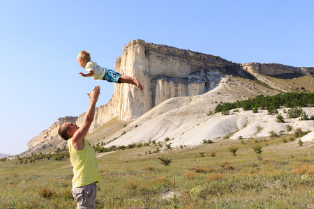 happy joyful father having fun throws up the little boy in the air against white cliffs in Crimea.