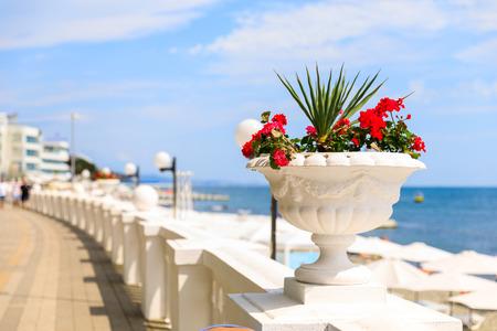 Schwarzmeerküste in Sotschi, leere Promenade und schneeweiße Retro-Zäune mit schönen Blumenvasen.