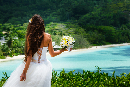 bride, beautiful young girl with dark hair in a white wedding dress with bouquet on  background of beach with blue water. Seychelles Stock fotó