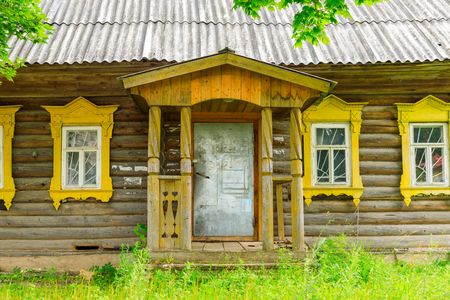 Wooden house withcarved platbands in the village of Yurino on the bank of the Volga. Russian traditional architecture lies in wooden houses with manually carved decorations, often painted in white. Stock Photo