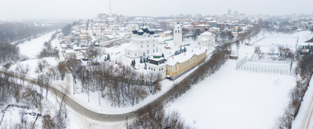 the city of Kirov and the high bank of the river Vyatka and the Alexander Grin Embankment and and Trifonov Monastery on a cloudy winter day.