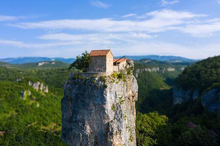Katskhi pillar. Alone man's monastery near the village of Katskhi. The orthodox church and the abbot cell on a rocky cliff. Imereti, Georgia.