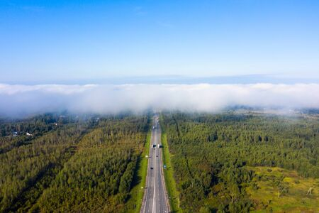 Beautiful hight way road high angle beautiful view of the fog over the road on an early summer morning in central Russia. Birds eye view of the road and skyline.