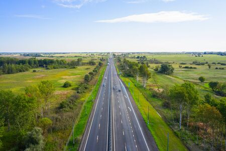 Beautiful hight way road on an early summer morning in central Russia. Moscow-Minsk M1 highway, Bird's eye view of the road and skyline. Foto de archivo - 132117393