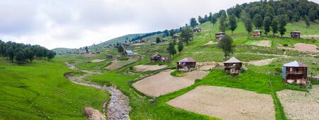 Beautiful nature with country cottages and traditional wooden houses on the road through the Goderdzi Pass in Georgia. Imagens