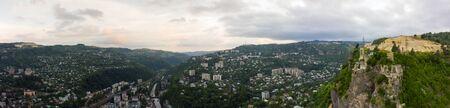 Anciennes cabines de téléphérique ou de téléphérique rouillées et fonctionnelles à Chiatura. Panorama du quartier de la ville et des immeubles à appartements sur le rocher et la mine à la station de téléphérique Rgani. Banque d'images