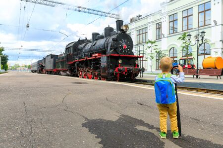 little boy tourist meets Old black steam locomotive in Russia on the background of the Moscow railway station. Standard-Bild