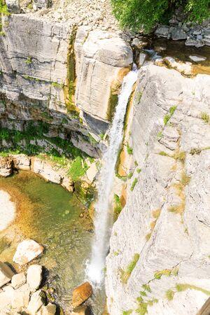 La cascade de Kinchkha dans le canyon de la rivière Okatse. Reste en Géorgie. Haute cascade dans la région d'Imereti. Corniches rocheuses de la montagne avec des arbres verts.