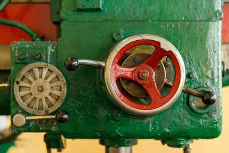 red controls of the Universal old and green drilling machine.